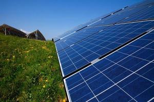 zonnepanelen, blauwe lucht en groen gras foto