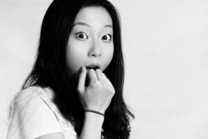 jonge vrouw voor haar mond foto