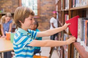 schattige leerling op zoek naar boeken in de bibliotheek foto