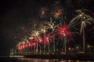 vuurwerk door water 's nachts foto
