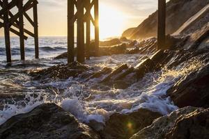 golven die op de kust onder dok breken foto