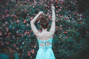 vrouw met opgeheven handen, tegenover rozenstruik foto