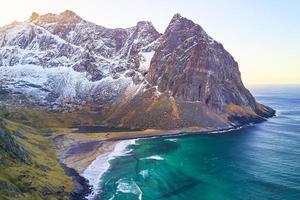 een strand bij een met sneeuw bedekte berg