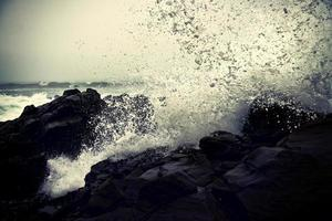 oceaangolven die overdag op rotsen beuken