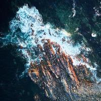 watergolven die overdag rotsen raken foto