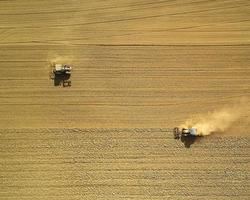 twee oogstmachines op bruin veld