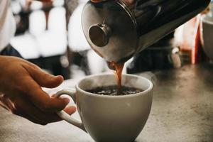 persoon koffie gieten in witte keramische beker foto