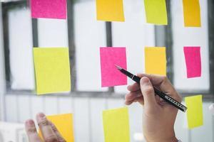 jonge creatieve professional met behulp van notities op glazen wand