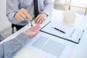 agent overhandigt de sleutel aan de klant foto