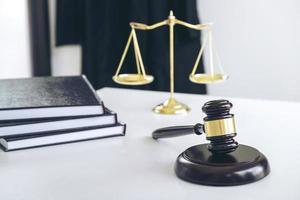 een hamer en schalen van rechtvaardigheid op wit bureaublad foto