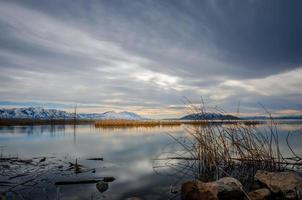 meer in de buurt van bergen in de schemering foto