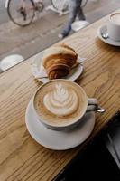 cappuccino en croissant op buitentafel foto