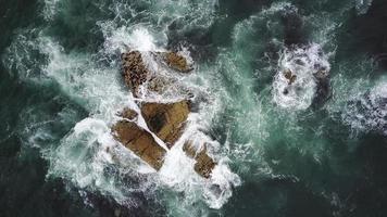 golven die op rotsen spatten foto