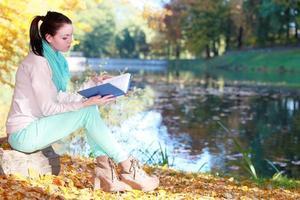 jong meisje ontspannen in herfst park leesboek foto