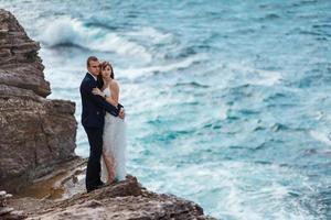 bruid en bruidegom in de buurt van de oceaan foto
