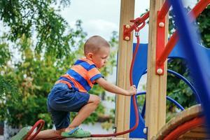 schattige kleine jongen spelen op de speelplaats in de zomer foto