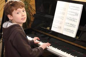 jongen speelt piano foto