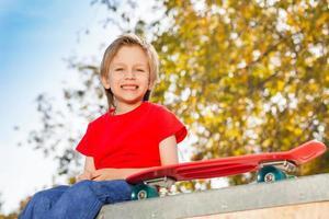 lachende blonde jongen zit met skateboard foto