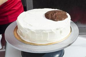 de vrouw begint cake met gesmolten chocolade te gieten foto
