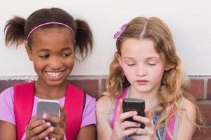 schattige leerlingen met behulp van mobiele telefoon