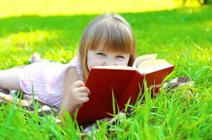 portret van klein lachend meisje kind met boek liegen foto