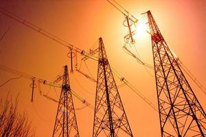 metalen hoogspanningsmast zendt elektriciteit uit op de hemelachtergrond stad foto