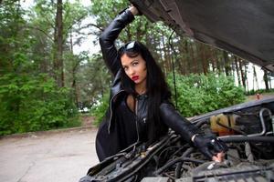 meisje bij de motorkap van de auto foto