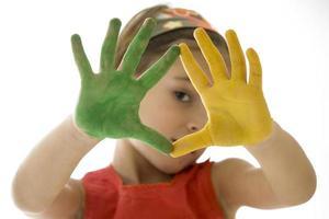 klein meisje met haar handen geschilderd foto