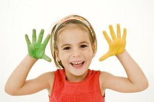 klein meisje met een hand groen geverfd en een geel foto