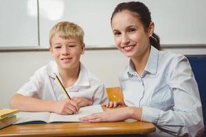 leraar helpt een student in de klas foto