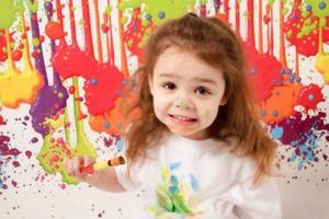 klein meisje speelt met verf
