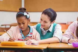 leraar helpt leerlingen tijdens de les foto