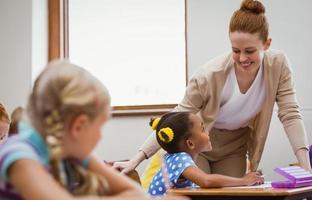leraar helpt een klein meisje tijdens de les foto