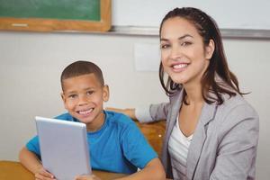 mooie leraar en leerling met tablet aan zijn bureau foto