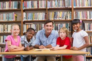 leraar en leerlingen glimlachen naar de camera foto