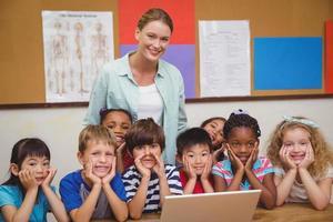 leraar en leerlingen die op laptop werken foto