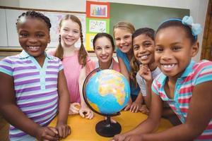 leraar en leerlingen kijken naar globe foto