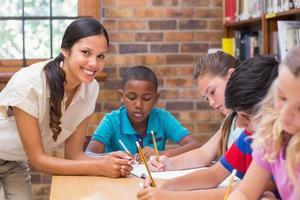 mooie leraar die leerlingen in bibliotheek helpt