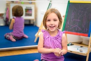 klein kind tekent met kleurkrijt op het krijt foto