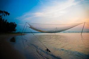 rustige scène van visnet tegen paarse zonsondergang.