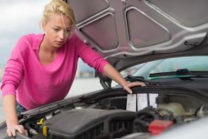 vrouw inspecteren gebroken automotor. foto