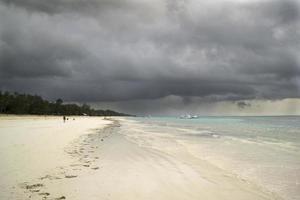 storm die zich verzamelt over een tropisch strand foto