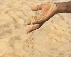 man met wat zand in de hand: droogte en woestijnvorming foto