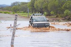 4wd oversteken overstroomde weg foto