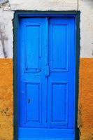 blauwe deur op gele muur
