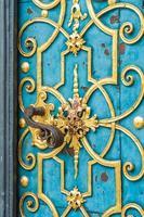 blauwe deur versierd met gouden versiering en handvat