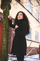 doordachte jonge vrouw in de buurt van boom op straat foto