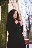 jonge vrouw in jas in de buurt van boom op straat foto