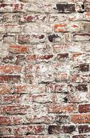 oude ongelijke vervallen witgekalkte sjofele bakstenen muur foto