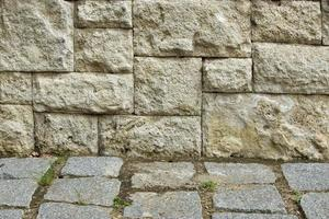 grijze stenen tegelmuur en kasseipadfragment foto